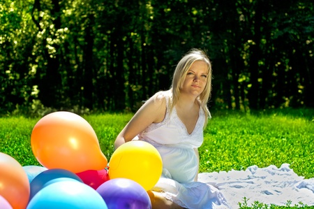 Attractive happy pregnant woman sitting and dreaming outdoors in colorful baloons Stock Photo