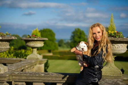 Beautiful blonde woman holding a cute english bulldog puppy dog
