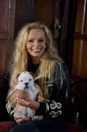 Blonde woman with an english bulldog puppy dog in luxury room Stock Photo - 20573784