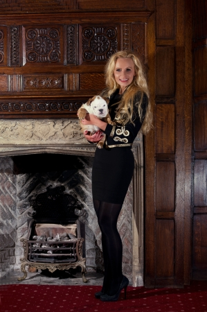 Blonde woman with an english bulldog puppy dog in luxury room Stock Photo - 20573761