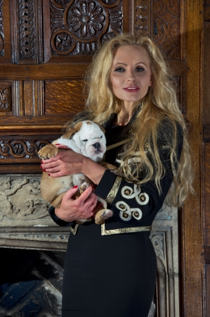 Blonde woman with an english bulldog puppy dog in luxury room Stock Photo - 20573762