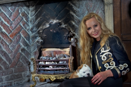 Woman sitting by a fireplace with a dog puppy in luxury interior Stock Photo - 20573760
