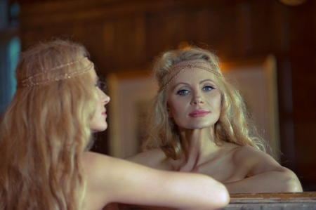 Beautiful blonde woman looking at herself in the mirror Stock Photo - 20573805