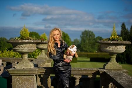 Beautiful blonde woman holding a cute english bulldog puppy dog photo