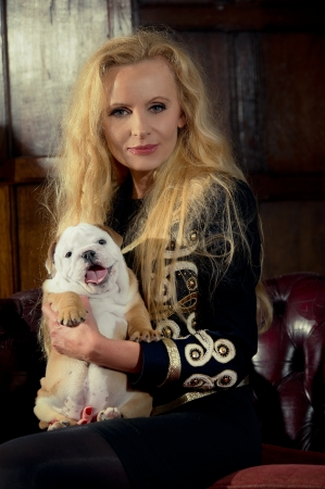 Blonde woman with an english bulldog puppy dog in luxury room photo