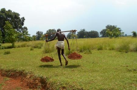 正午で、老人のキャリング重い土