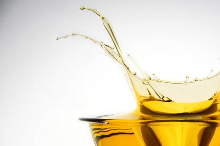 Vista lateral del aceite de cocina que salpica en el envase, fondo del estudio.