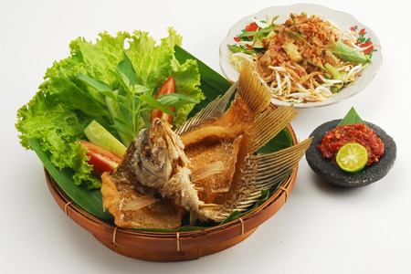 Closeup of fried gourami fish meal with side salads, isolated on white background.