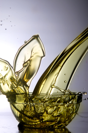 Liquid cooking oil splashes when poured into a full glass bowl.