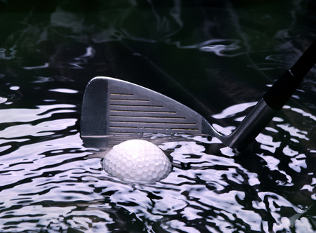 Golf ball in a water hazard with iron club Reklamní fotografie