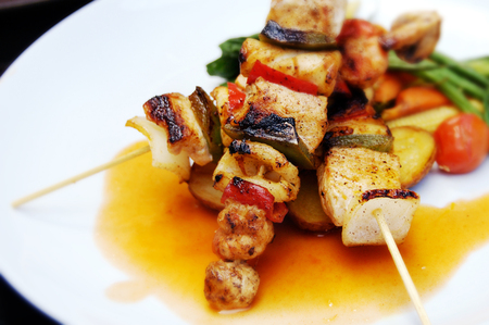 Grilled seafoods and vegetable skewers with sauce on a white plate.