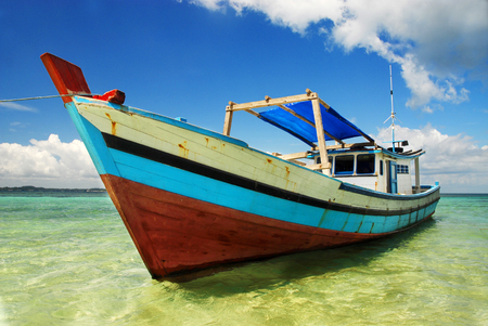A colorful wooden boat moored on a beach at Belitung Island, Indonesia.