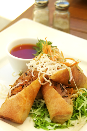 A spring roll dish served with chilli sauce on vegetable, and topped with fried rice noodle Reklamní fotografie