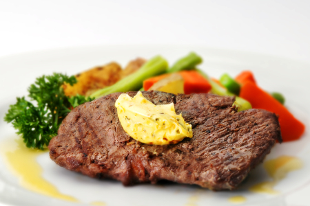 A fried tenderloin steak with butter and various vegetables on a plate.