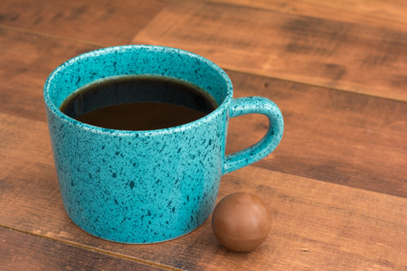 Teal coffee cup full of black coffee and chocolate balls on wooden background. Stock Photo