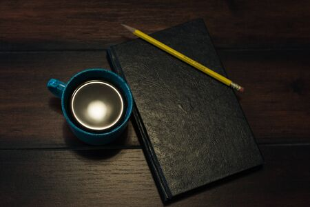Teal coffee cup full of black coffee on wooden background and notebook.