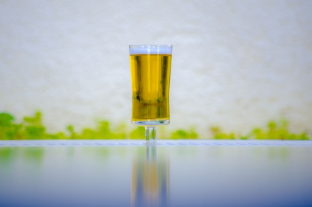 near beer: a glass of cold beer near pool