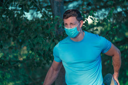Young caucasian man with mask and blue shirt doing stretching on the fence of a park with trees in the background