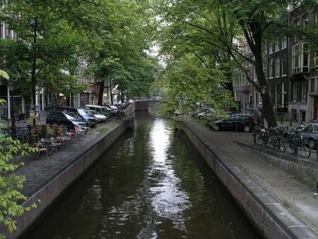 Amsterdam canal under canopy of trees
