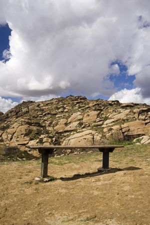 bench against rocks and clouds in regional park Imagens