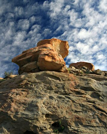 dramatic red rock above blue sky with clouds