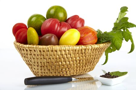 A basket with a variety of organic tomatoes, a dish with peppercorns on a white background. photo