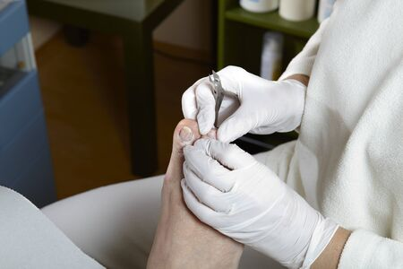 A Podiatrist cut the toenails on of a women photo