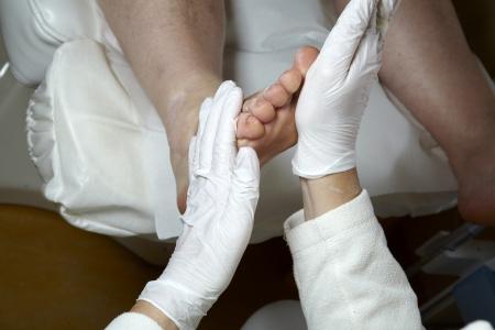 A Podiatrist gives a woman a leg and foot reflexology