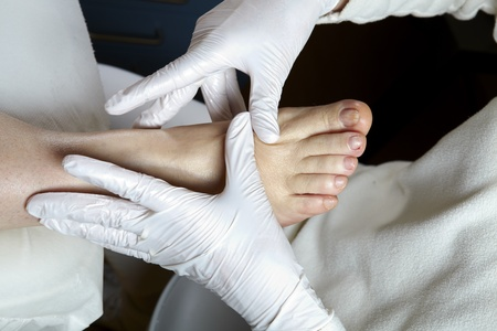 A Podiatrist gives a woman a leg and foot reflexology photo