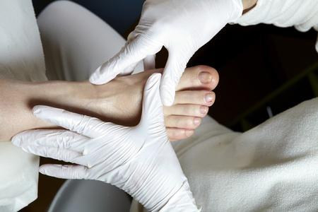 A Podiatrist gives a woman a leg and foot reflexology photo