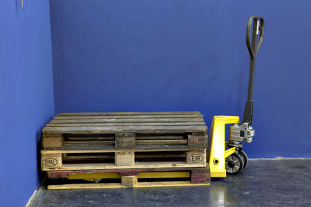 sacktruck: Three wooden Pallets on a yellow lift truck in a industry hall Stock Photo