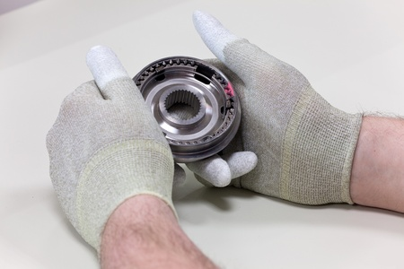 introduces: A Employee introduces a visual inspection of a synchronizer ring Stock Photo