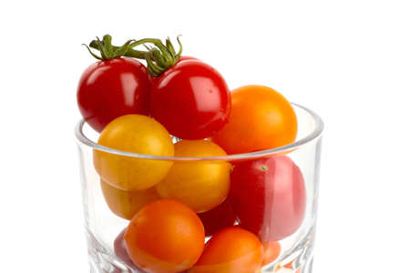 A glass filled with colorful small organic tomatoes in front of white background photo