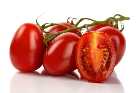 Fresh roma tomatoes cut in front of white background