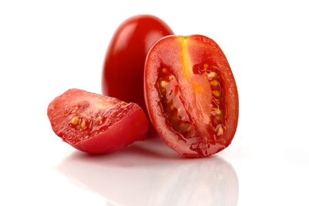 Fresh roma tomatoes cut in front of white background photo