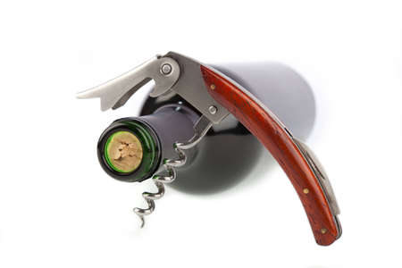 Corkscrew opened in front of a wine bottle photo