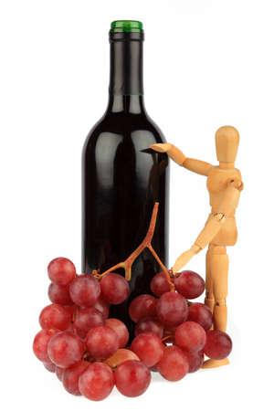 marioneta de madera: Mu�eco de madera se encuentra junto a una botella de vino con uvas