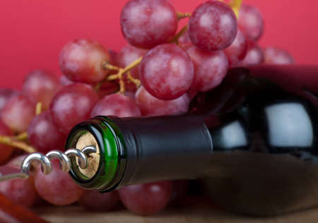 Wine bottle with corkscrew is in front of red grapes Stock Photo - 12829677