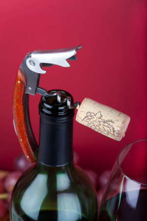 bottleneck: A corkscrew with cork on the top of bottleneck beside of a glass of red wine Stock Photo
