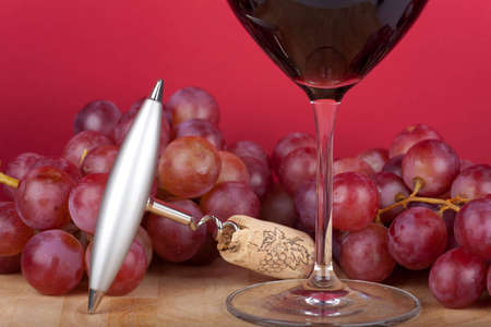 Metal corkscrew with cork lying in front of a glass of red wine photo