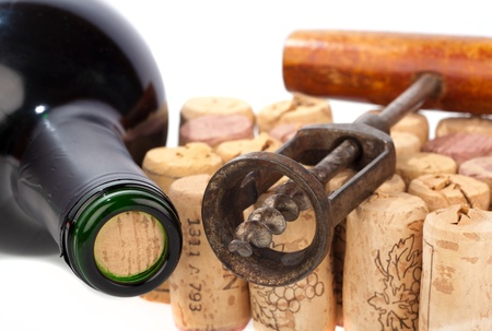 Older corkscrew lies on some corks beside a wine bottle photo
