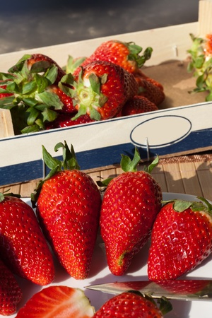 Fresh red Strawberries in a box and some on a plate photo