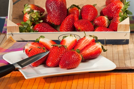 Fresh red Strawberries and slices on a plate with a knife photo