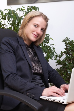 Business woman sitting and working with notebook on her knees photo
