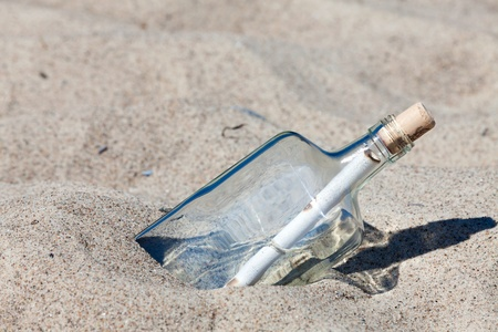 Message in a bottle stuck in sand on the beach of the Baltic Sea photo