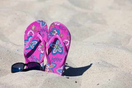 A pair pink colored Flip-Flops in the sand with a black sunglasses photo
