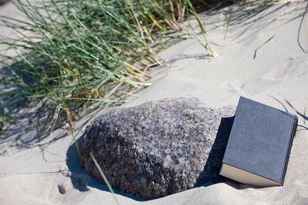 Un libro cerrado se encuentra en la arena en una piedra Foto de archivo - 13967684