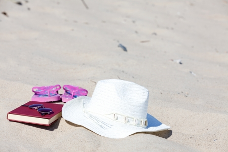 With the straw hat and a book on the beach photo