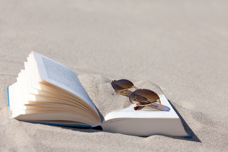 Sunglasses with brown tinted lenses lies on an opened book on the beach Stock Photo - 13967592