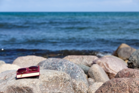 Closed Book with dark tinted sun glasses lies on a rock on the beach Stock Photo - 13967662